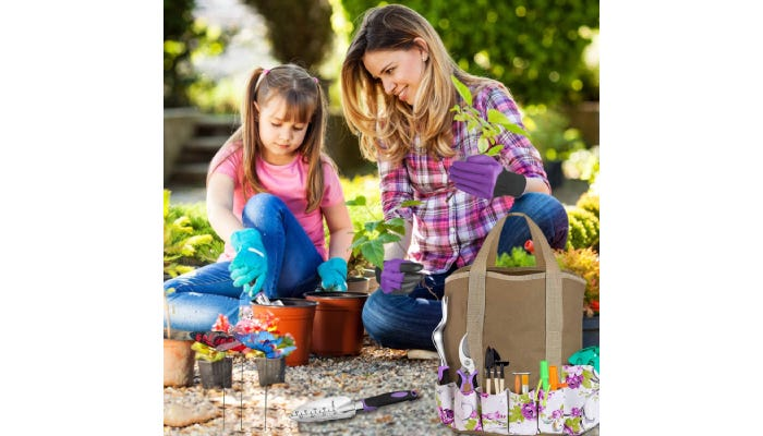 Woman and a little girl using tools to place a plant in a pot.