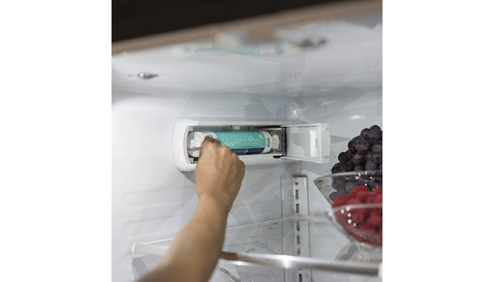 Hand reaching inside refrigerator to replace filter