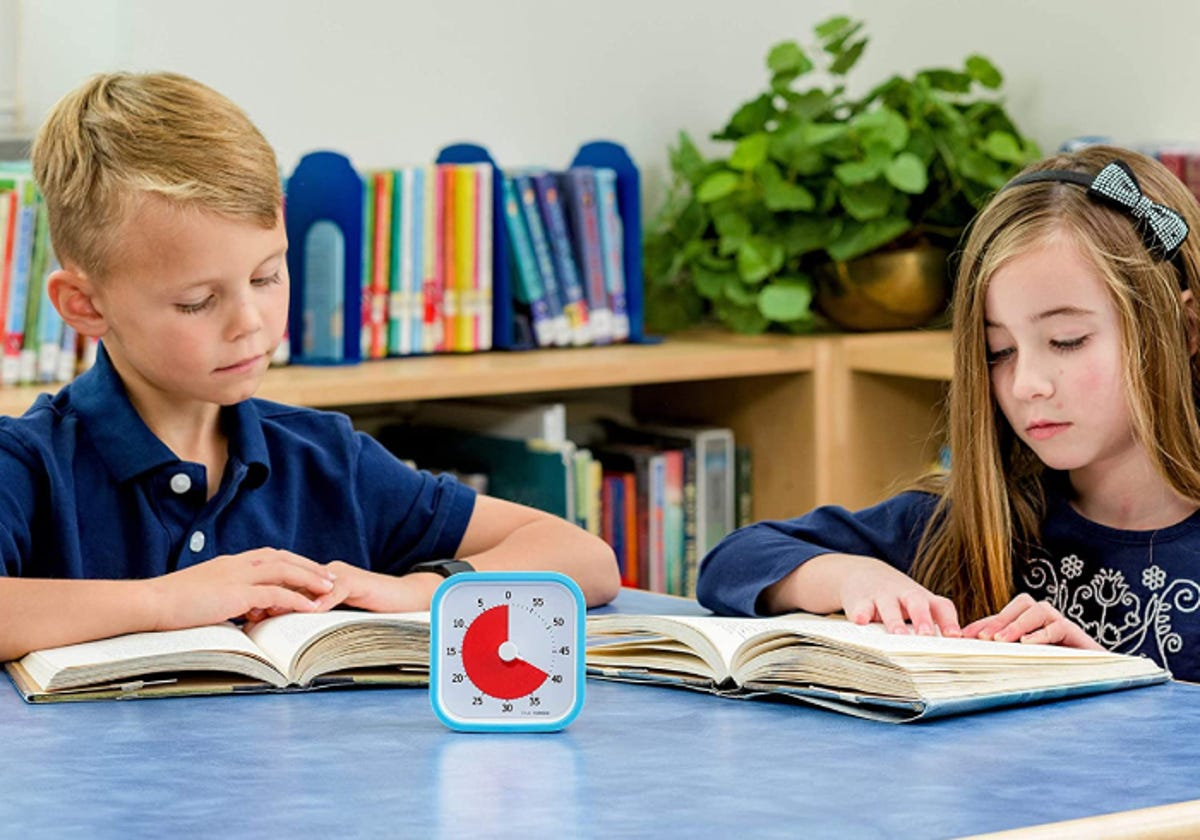 two children reading books in a classroom with a timer resting in front of them