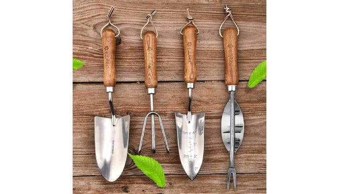 Four silver gardening tools hanging from wooden wall.