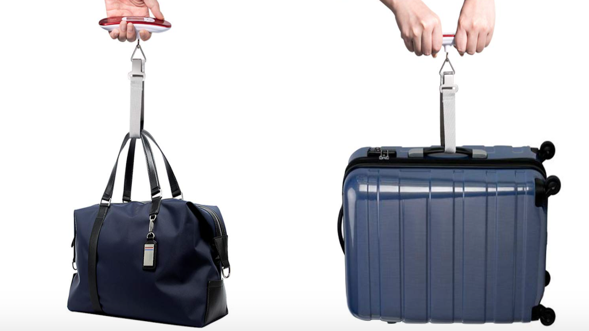 Two handheld luggage scales, one weighing a dark blue duffel bag and one weighing a dark blue rolling suitcase.