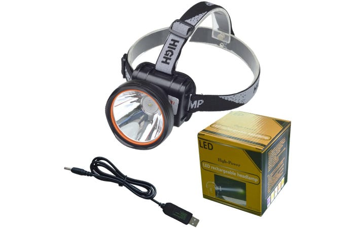 a headlamp with one large bulb at the front of it and a charger cord