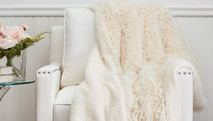 a furry cream-colored Sherpa blanket draped on a white chair