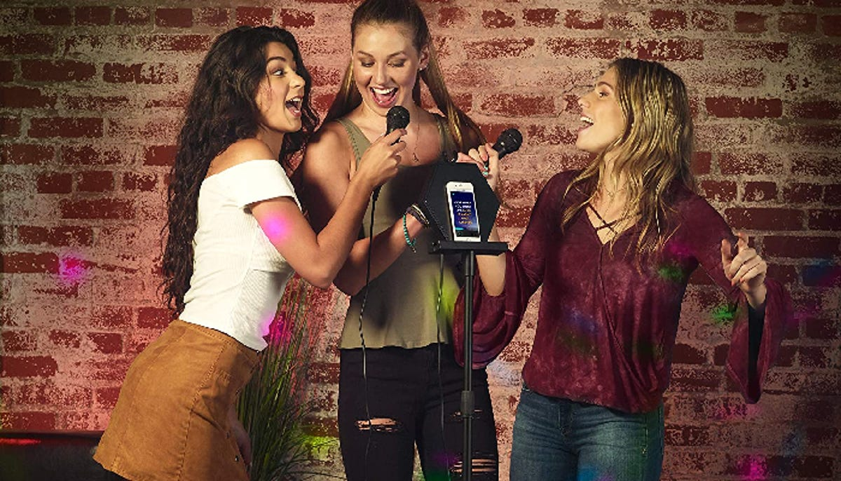 Three women standing in front of a brick wall backdrop sing karaoke while sharing two microphones.