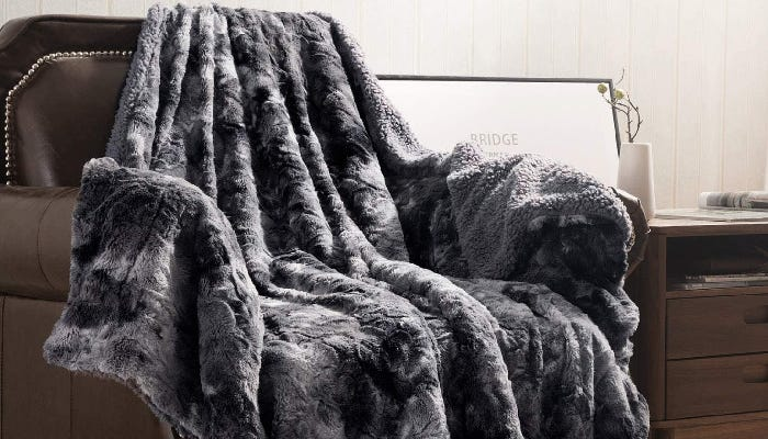 a dark gray Sherpa blanket draped on a brown accent chair