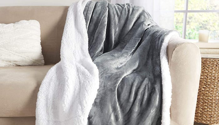 a gray and white Sherpa throw blanket draped on a couch