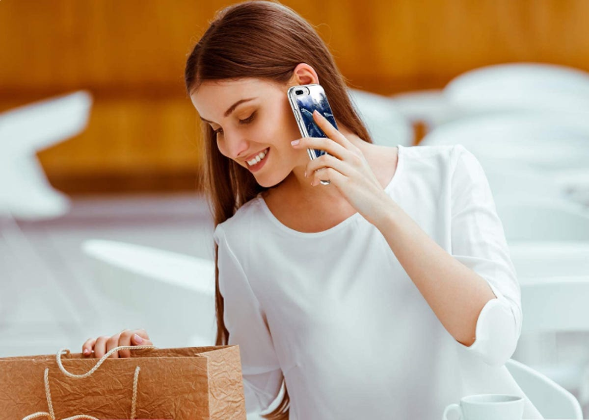 a woman holding her iPhone with a case to her ear and looking at a bag