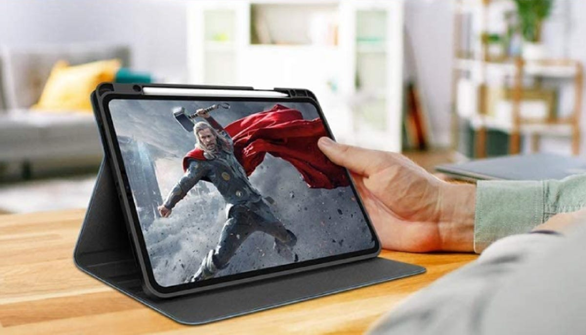 a hand holding an iPad that's playing a movie