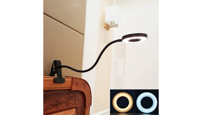 Clamp-on reading light mounted to headboard of a bed. Two light settings are displayed