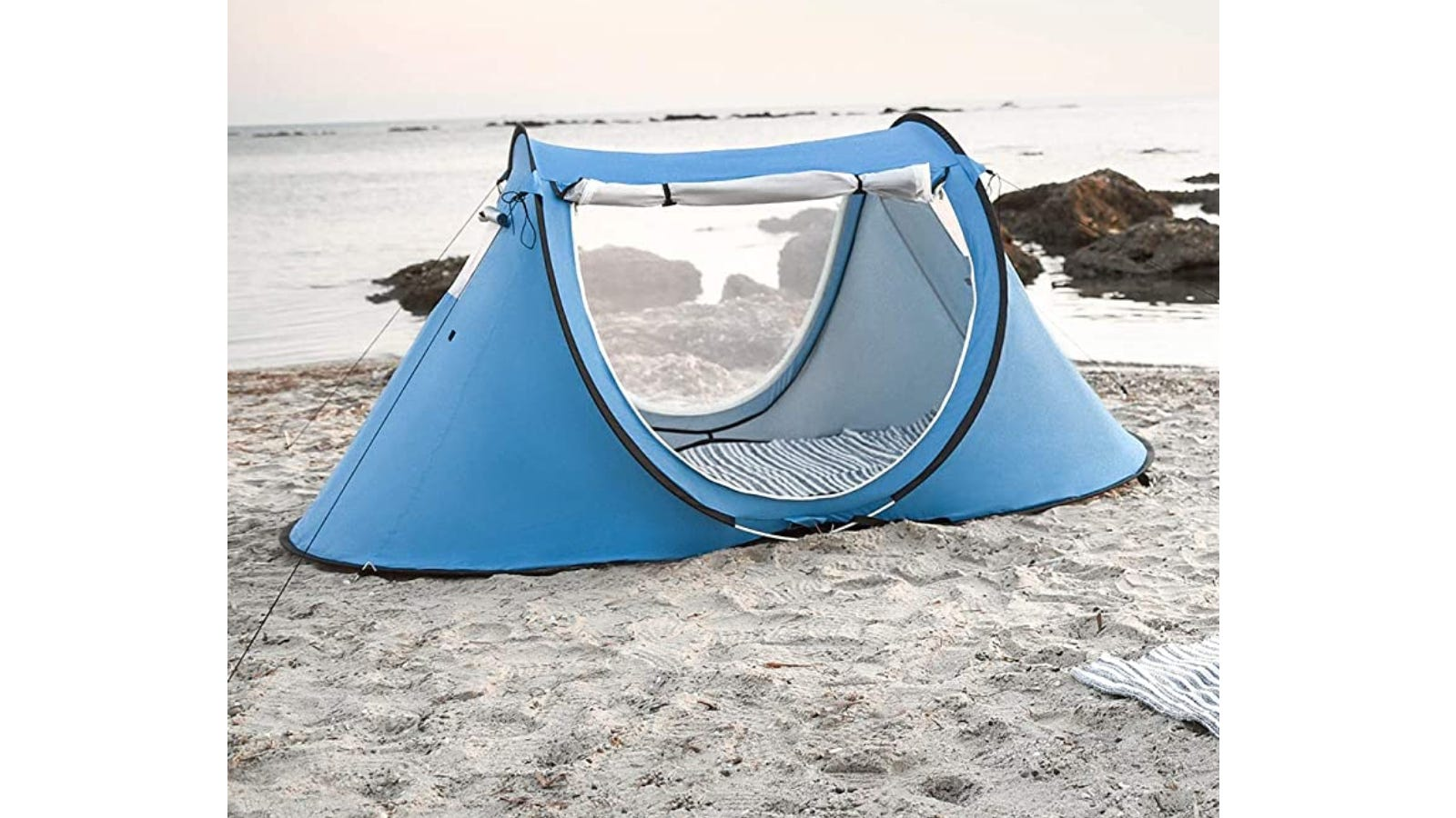 A blue mosquito net tent sitting on the sand of a beach.