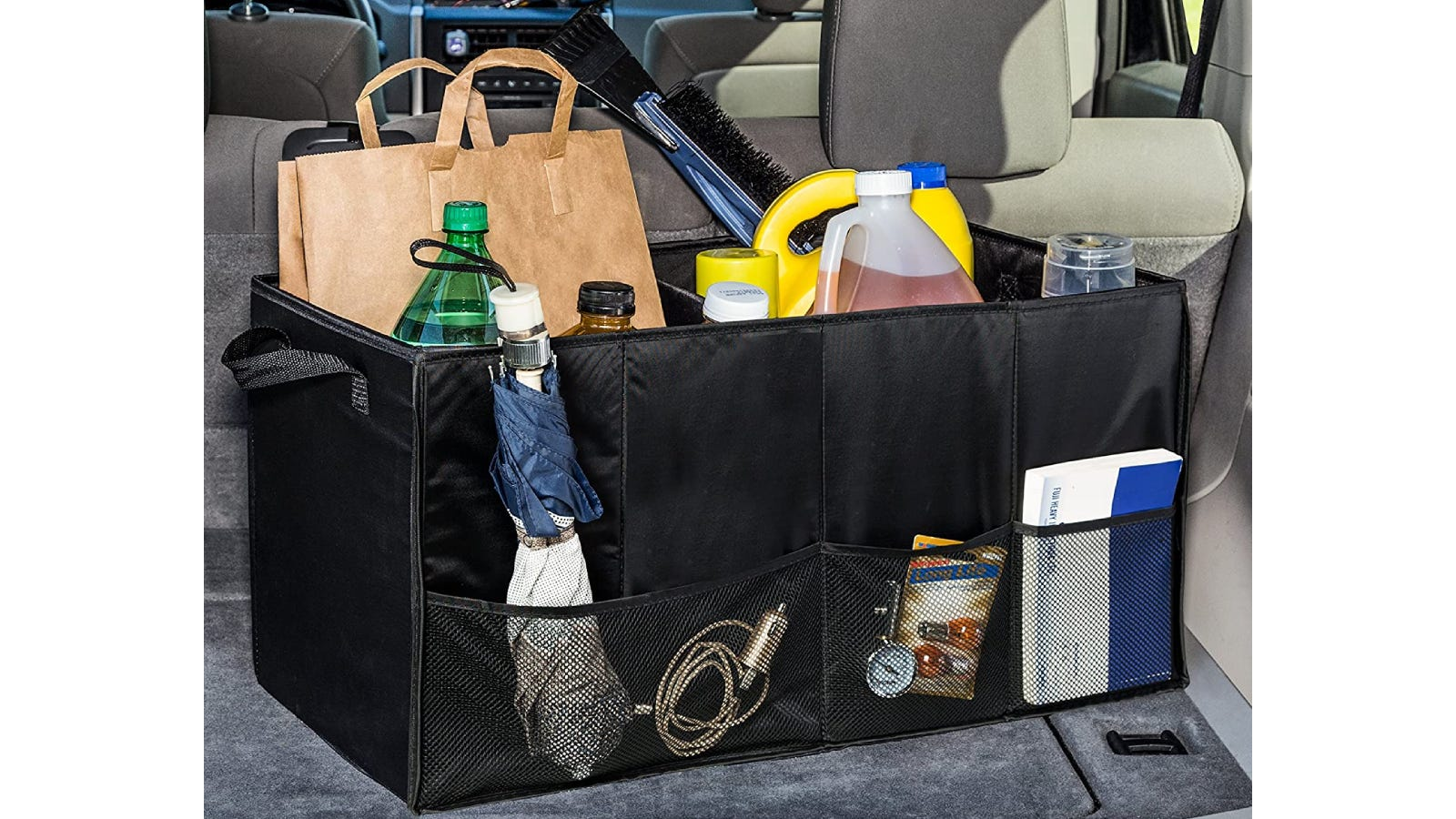 A black two-compartment trunk storage organizer filled with items and sitting in a trunk.