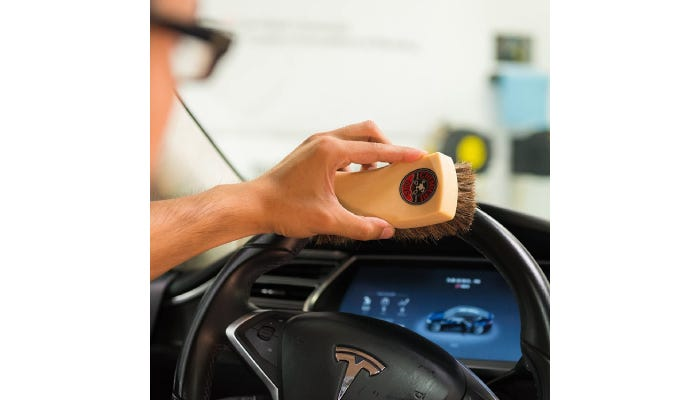 A person brushing their steering wheel with a horse hair brush.