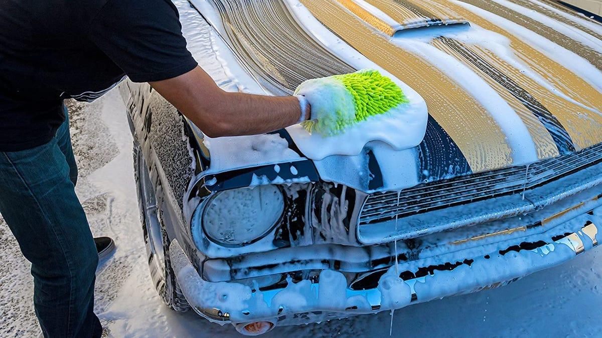 A man washing a car with a neon green washing mitt.