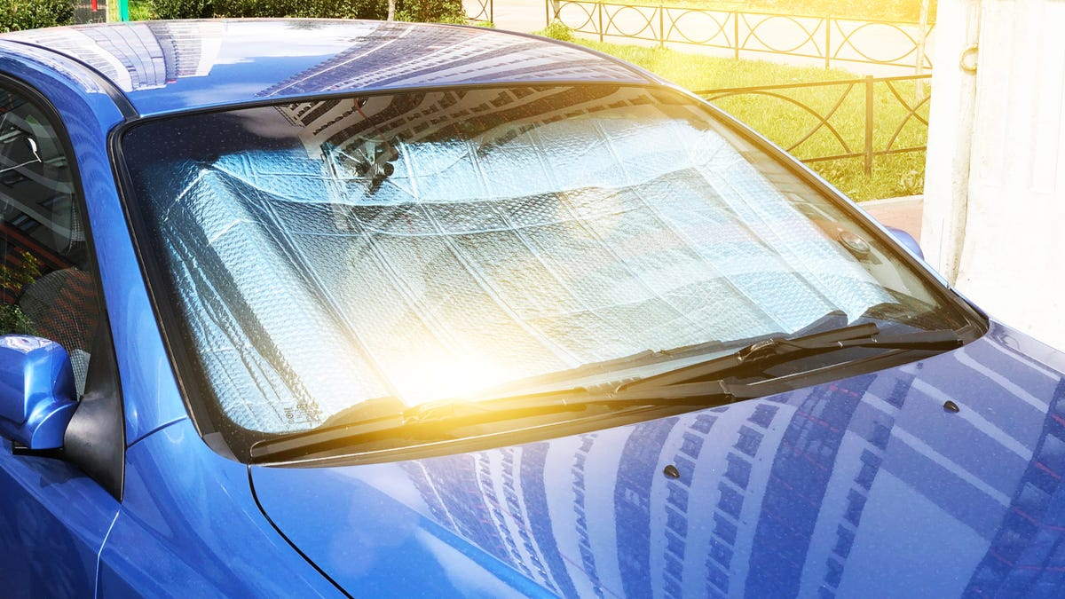 Protective reflective surface under the windshield of the passenger car parked on a hot day, heated by the sun's rays inside the car.