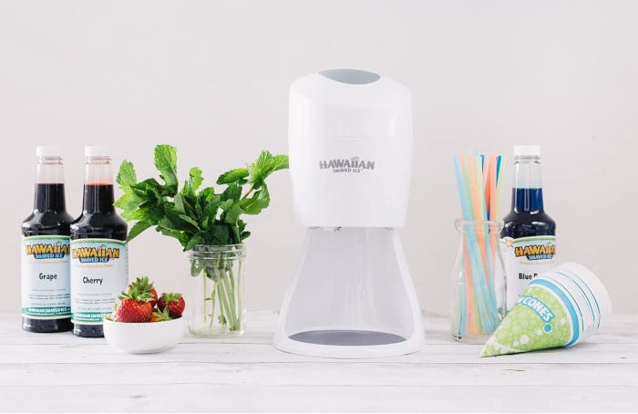 Compact white snow cone machine with three flavor syrups, paper cones, and straws.