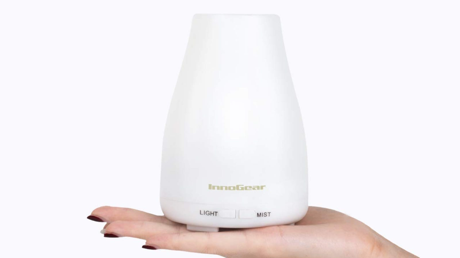A women holds a white oblong diffuser in the palm of her hand.