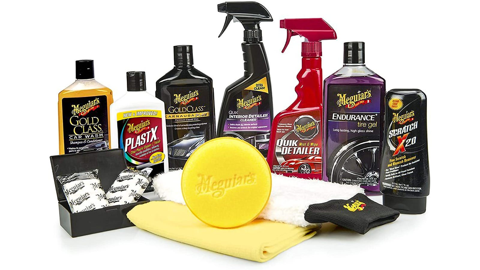 Seven bottles of car cleaning products lined up with towels, a clay bar, and other products in front of them.