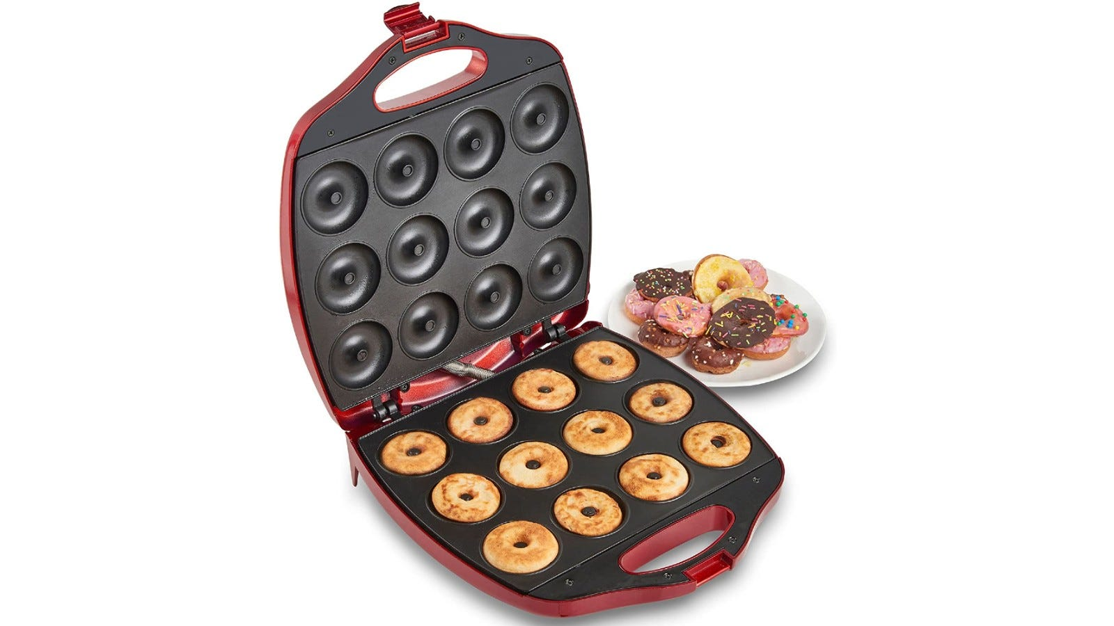 A large donut machine with 12 donuts cooking inside and finished donuts on a plate in the background