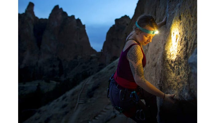 A woman climbing a side of a mountain while wearing her bright headlamp.