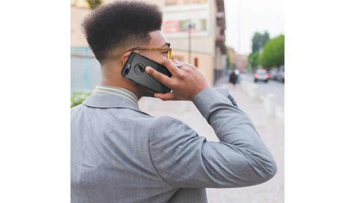 A man looking off into the distance while talking on his iPhone.