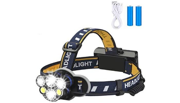 A headlamp shown with batteries and a USB cable which are both included.