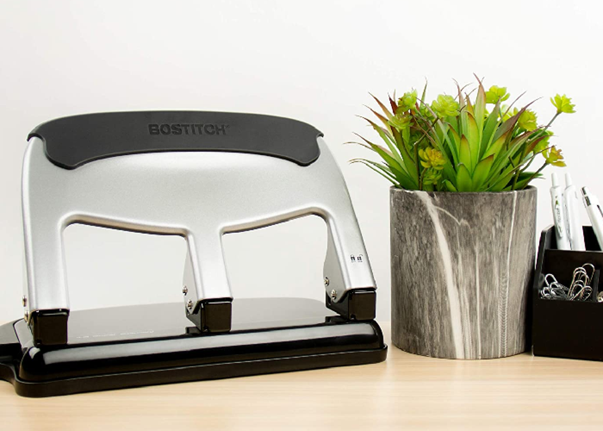 A three hole punch on a desk next to a fake plant and basket with paper clips