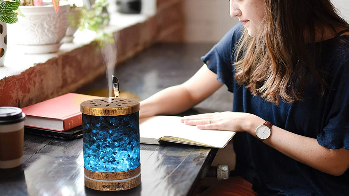 A brunette women writes in a notebook on a black desk while Himalayan salt diffuser expels vaper.