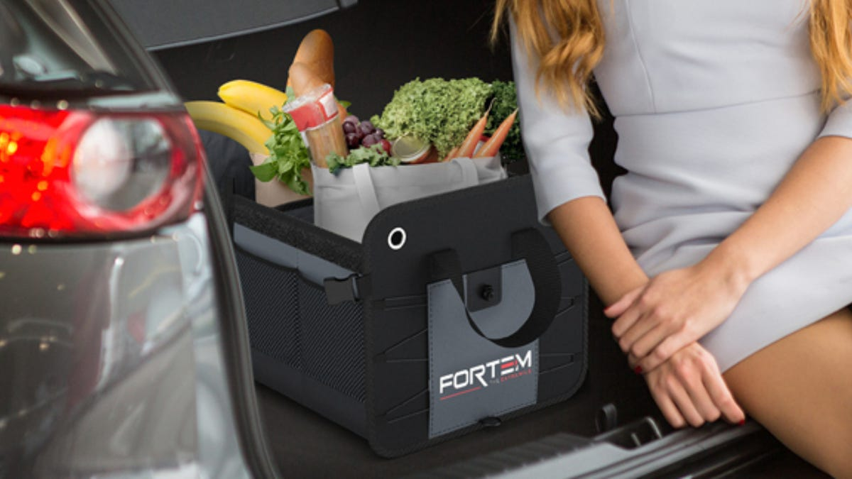 A woman wearing a grey dress sits in the trunk of car next to a black storage organizer that contains groceries.