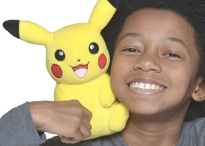 Pikachu plush resting on a young boy's shoulder.