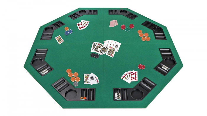 A dark green poker table top with poker chips and playing cards.