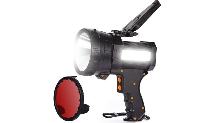 A 1.12-pound black spotlight with orange-button detailing as well as a side floodlight and a collapsible tripod on top, is propped next to a separate red lens.