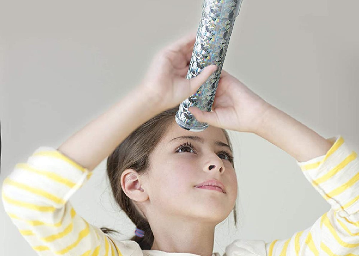 a girl in a striped shirt looking through a silvery kaleidoscope
