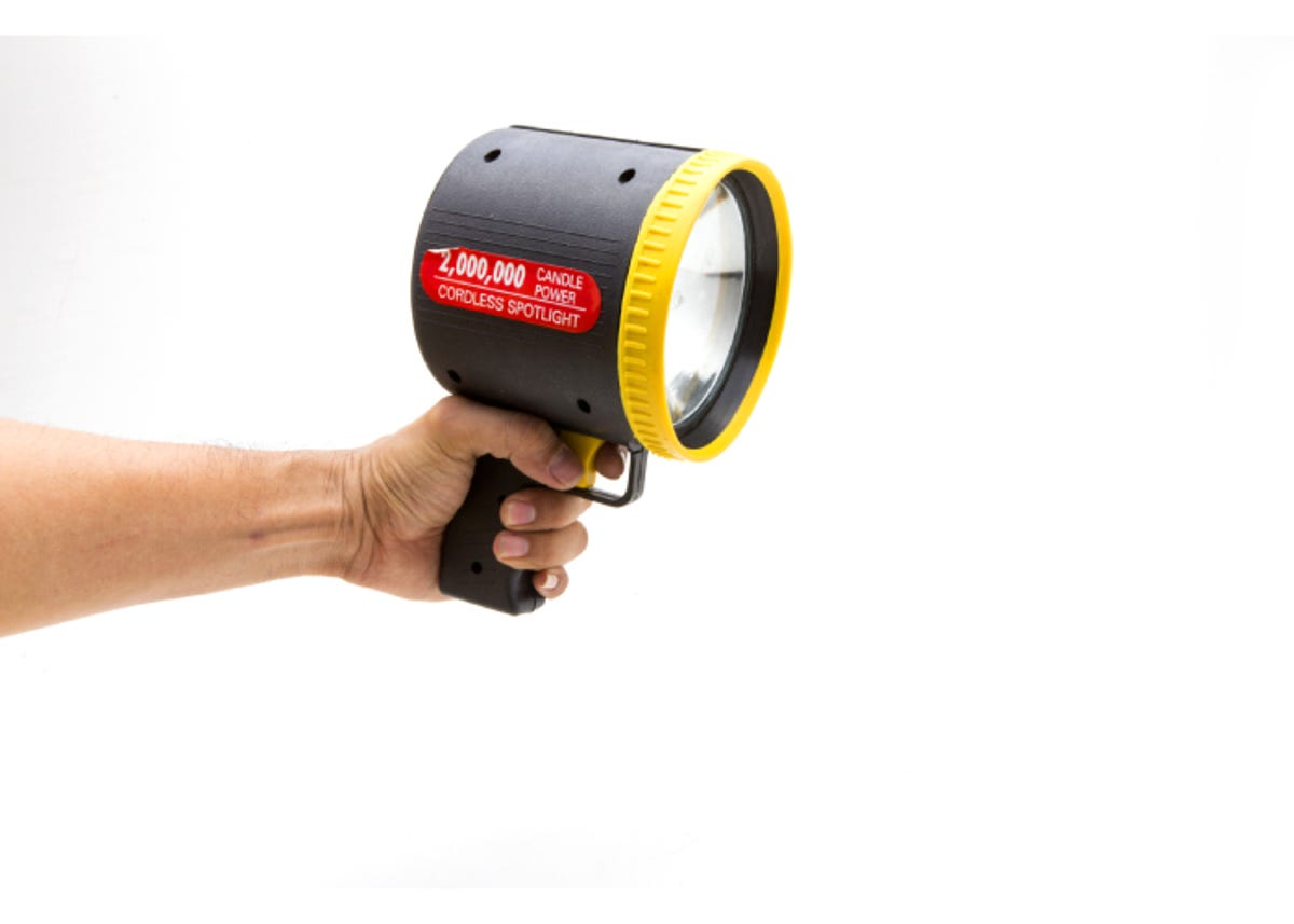 a hand holding a flashlight spotlight with a white background