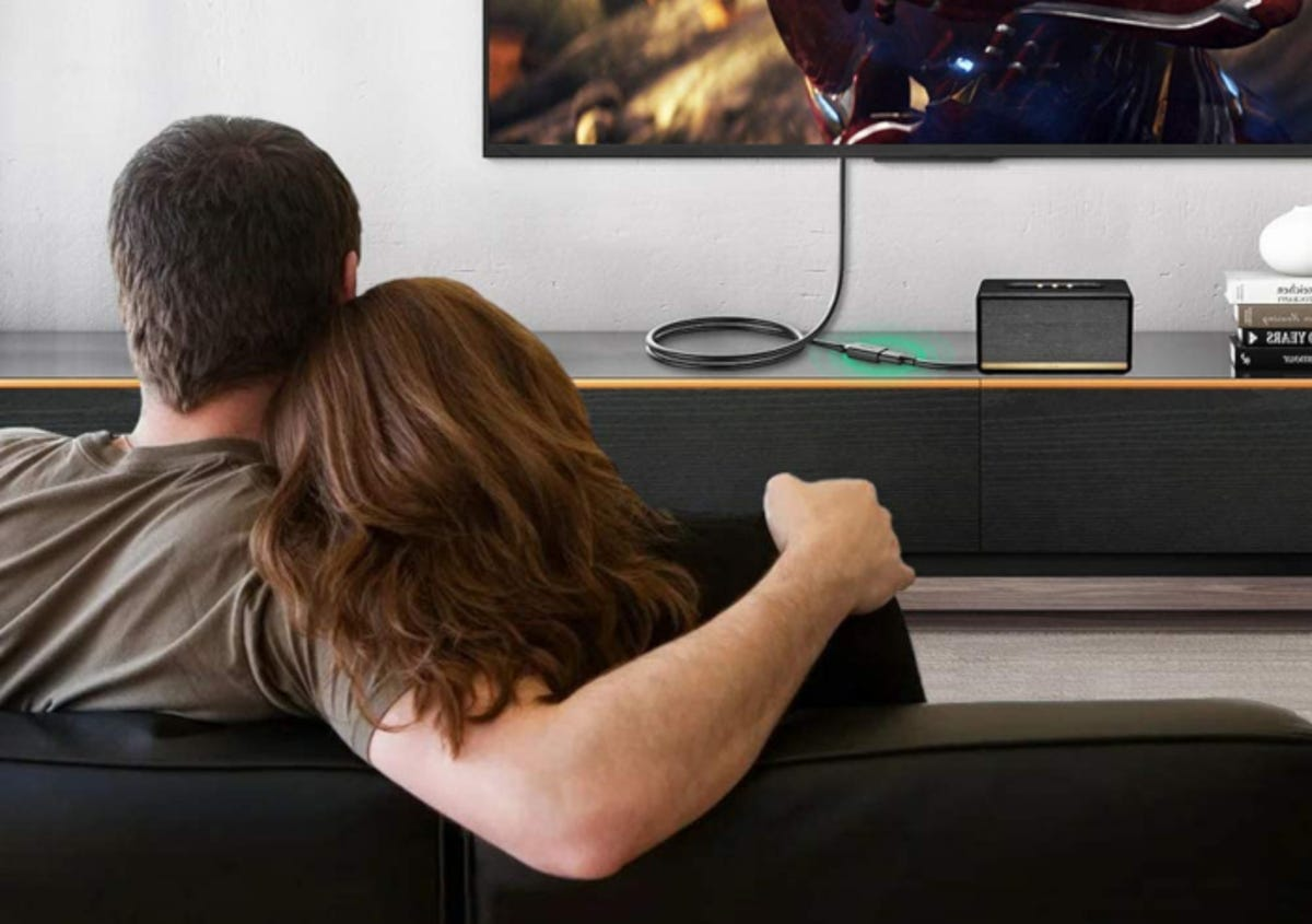 Man and woman watching a television that is attached to a USB extension cable and speaker device