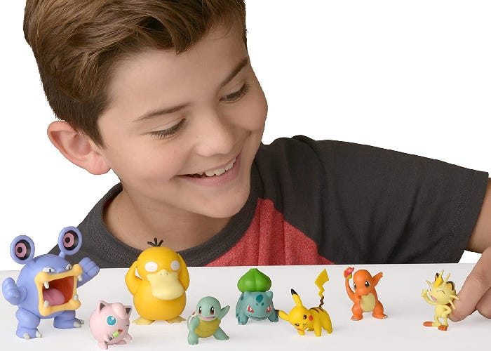 A young boy playing with the eight Pokemon figurines in the set.