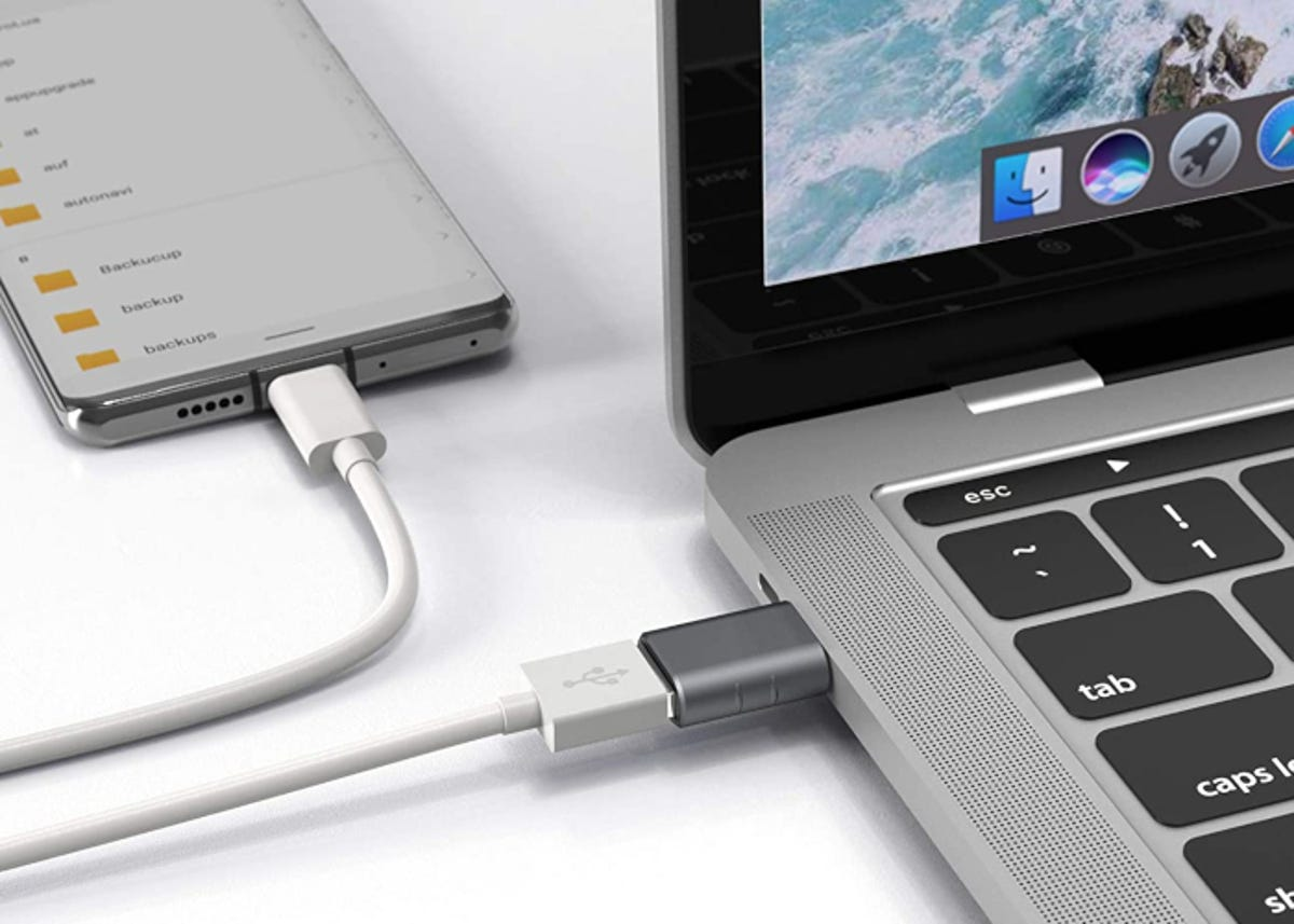USB-C to USB adapter connecting USB cable from a phone to a Apple laptop.
