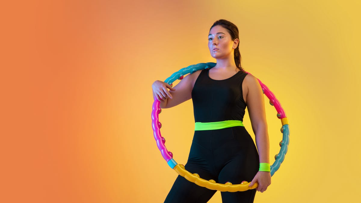 A young female dressed in black work out clothing holds a colorful hula hoop against a gradient orange to peach background.