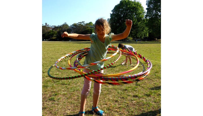 Girl hula hooping outside with many hoops at once.