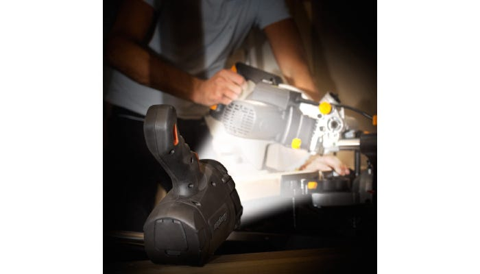 A one-pound black spotlight is flipped onto the flat side of its head to illuminate a man using heavy machinery in the dark.