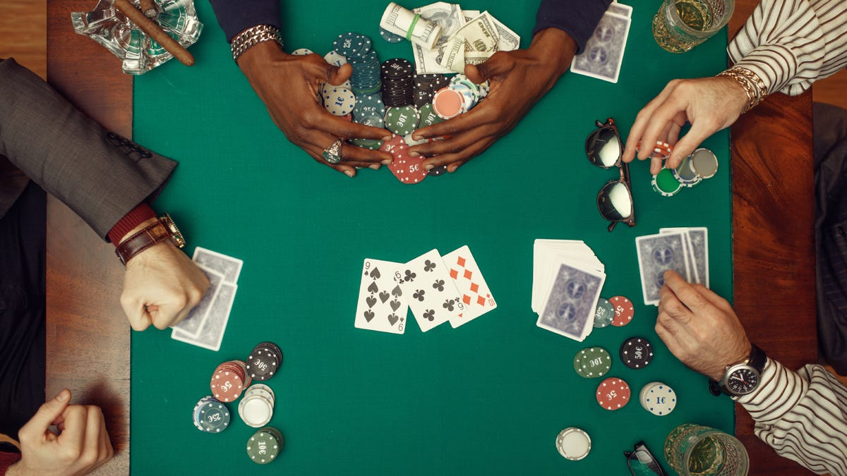 A top view of poker players hands with cards and chips on a green poker table top.
