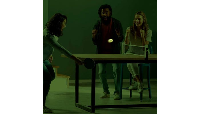 People playing ping pong in the dark with a glow-in-the-dark ping pong ball.
