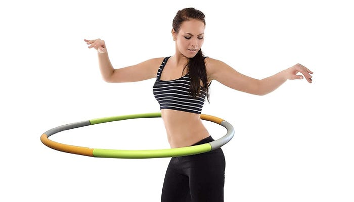 A woman raises her arms while hula hooping with an orange, green, and grey hula hoop.
