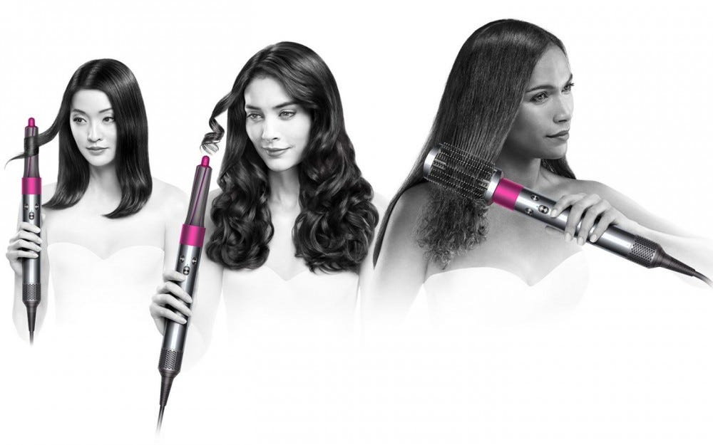 Three women styling their hair with the Dyson Airwrap Styler.