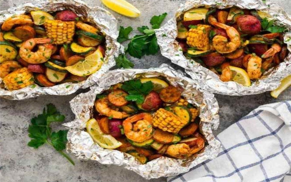 three foil dinners each holding, shrimp, corn, chicken sausage, potatoes zucchini and lemon.