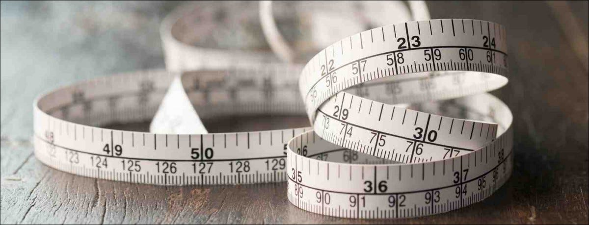 Close up tailor measuring tape on wooden table background