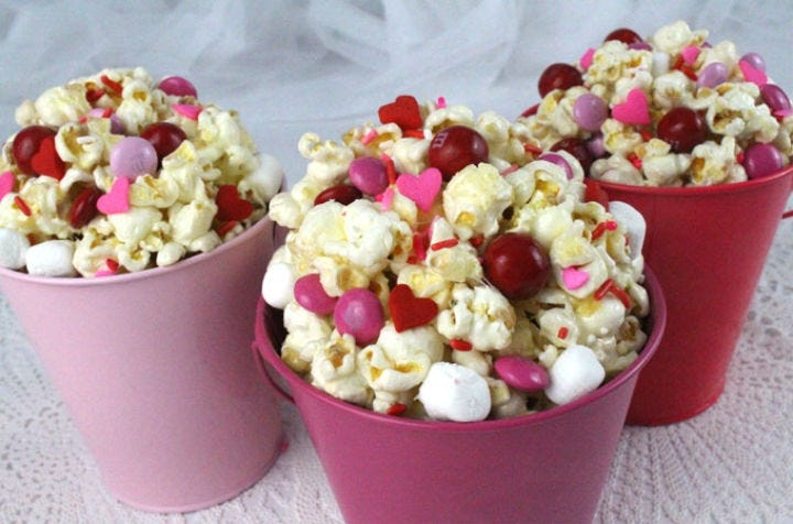 Three small red and pink buckets filled with popcorn and pink and red candies.