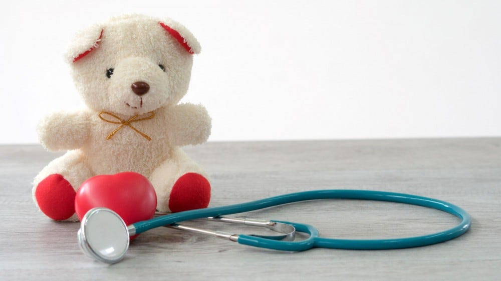 Valentines Day teddy bear sitting next to a stethoscope.
