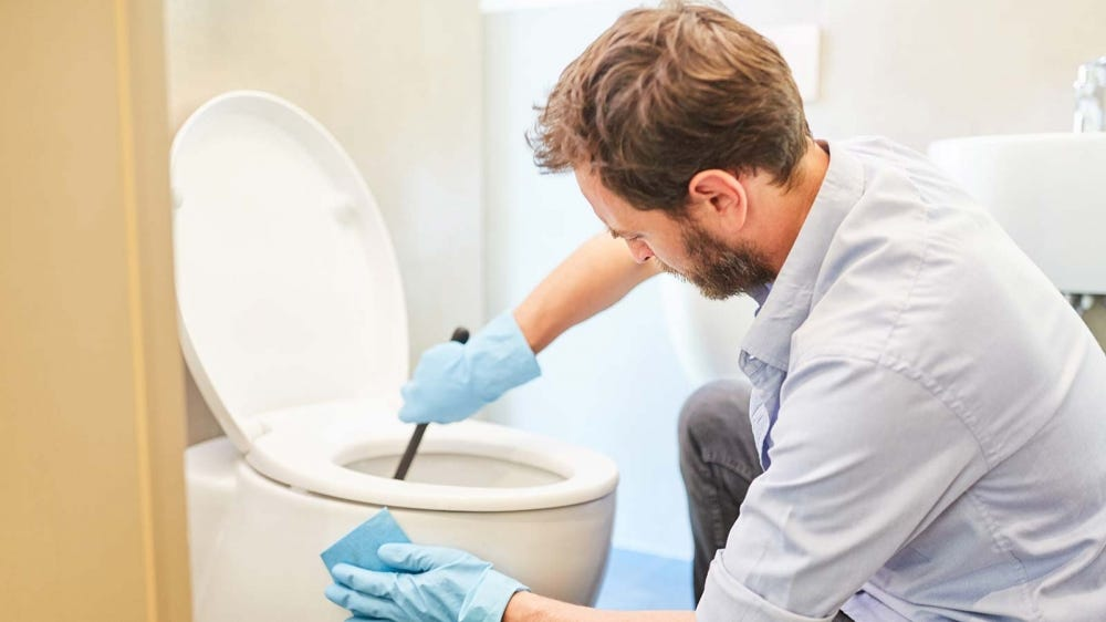 A man scrubbing the toilet in his bathroom with a cleaning brush, wearing rubber gloves.