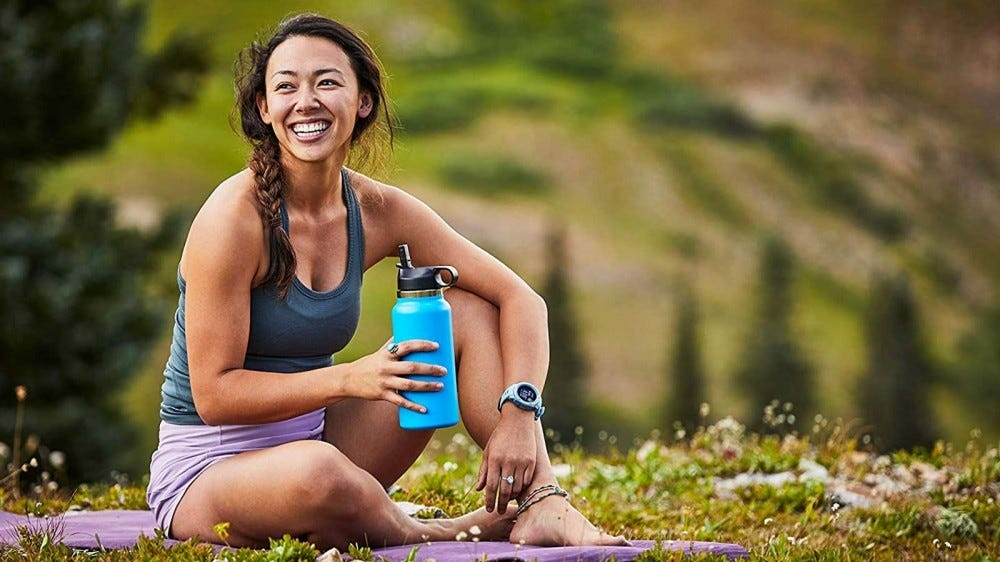 A woman sitting on a yoga mat, holding a Hydro Flask water bottle.
