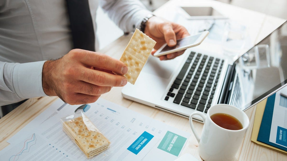 Man snacking on crackers while working on his laptop.